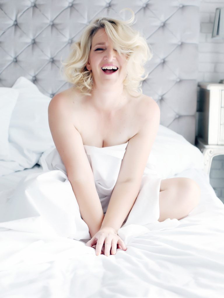 Laughing blonde lady during a boudoir photo session