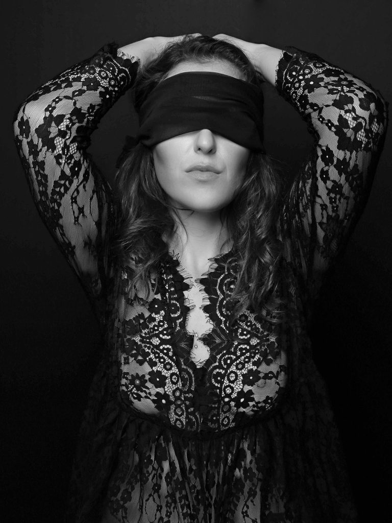 Woman wearing a blindfold during a boudoir photography portrait session