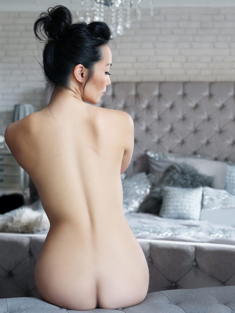 Naked woman with dark hair sitting near a bed