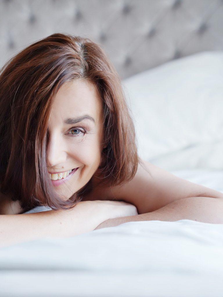 Smily confident woman during a boudoir photoshoot