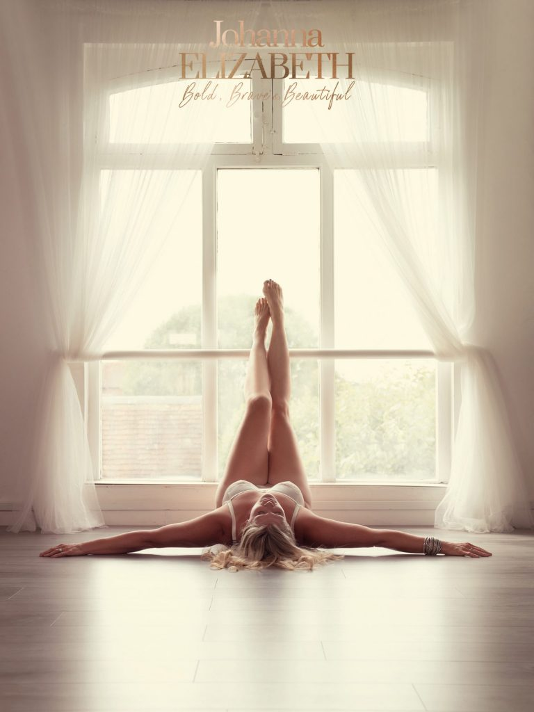 Blonde lady lying on the floor near a window during a boudoir photoshoot