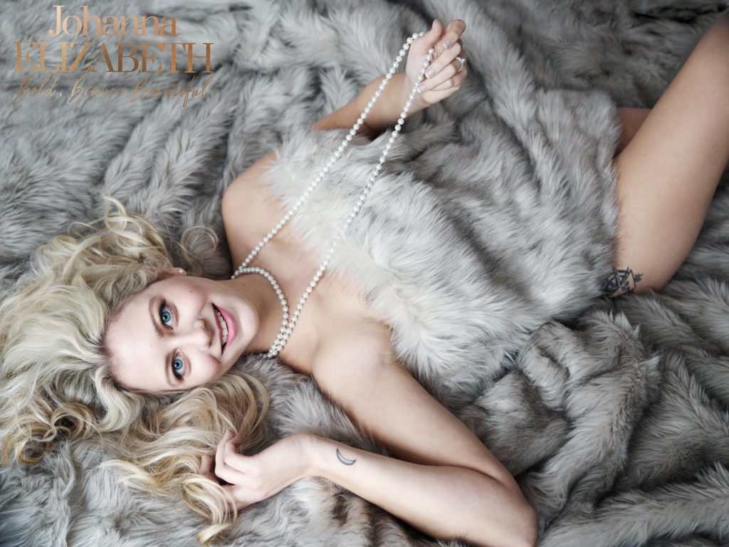 Smiling blonde woman reclining on bed wearing beads