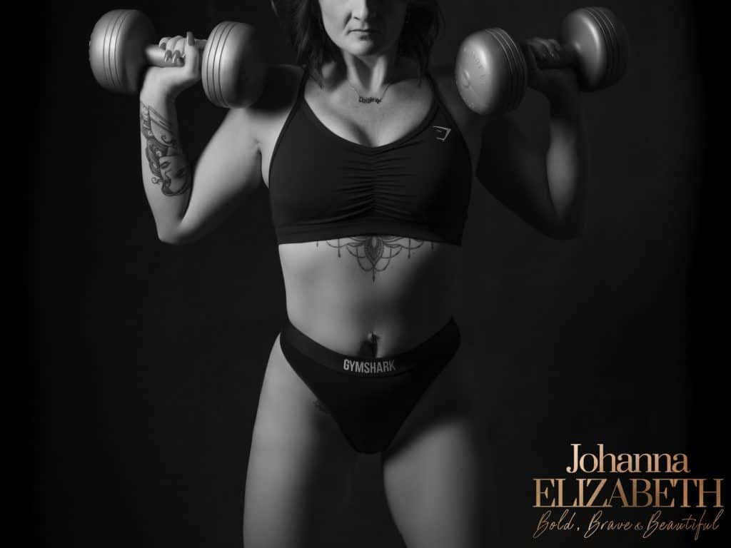 Woman lifting weights during boudoir photography portrait session