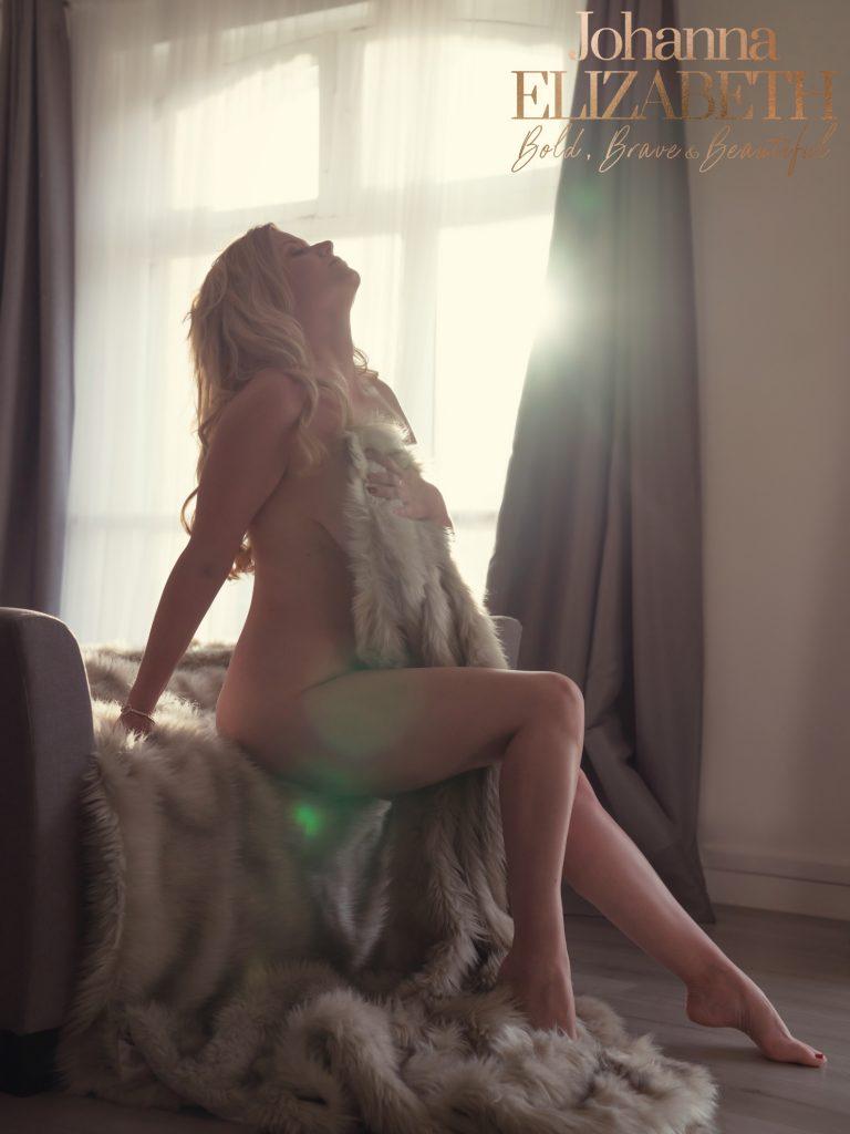 Empowered woman sitting near a window during a boudoir shoot