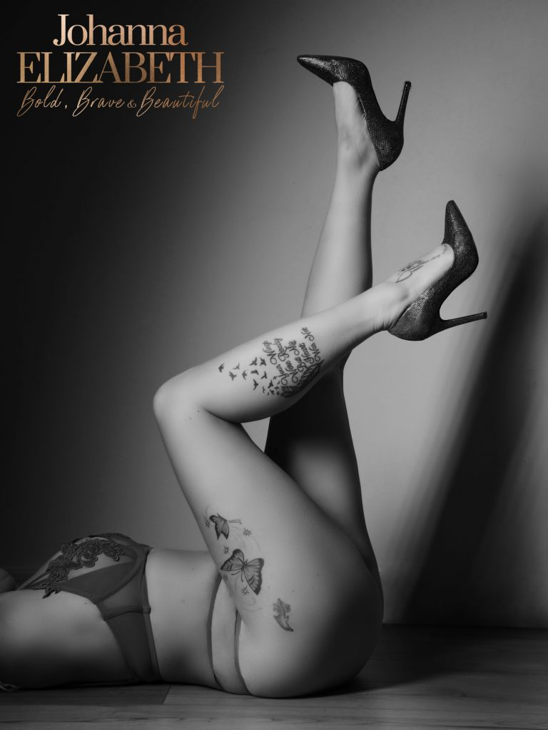 Tattood lady wearing heels with legs in the air