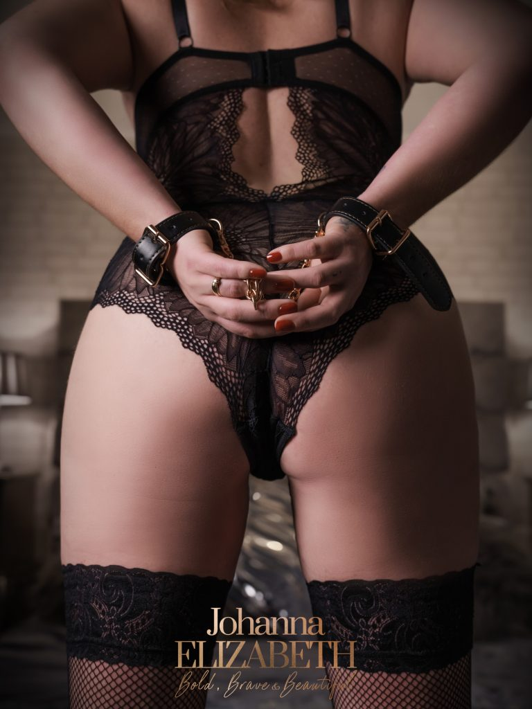 Woman wearing black lace underwear during a boudoir photoshoot