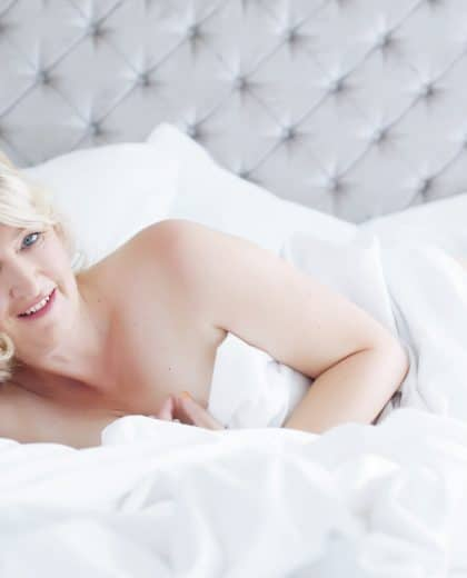 Smiling woman on white bed sheets