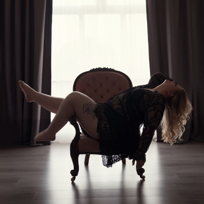 Woman laying back on a chair wearing a black robe