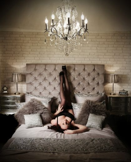 Woman reclining on a bed wearing suspenders