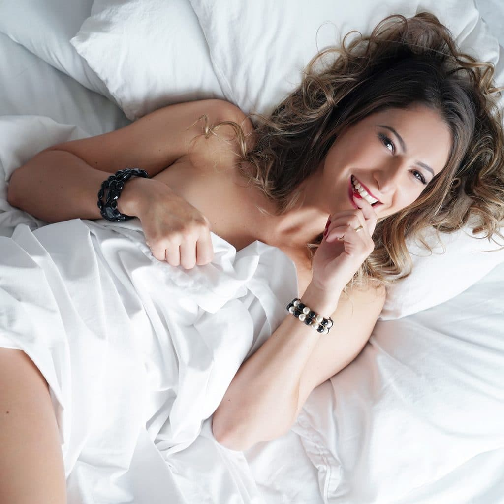 Smiling brunette wrapped in white bedsheets
