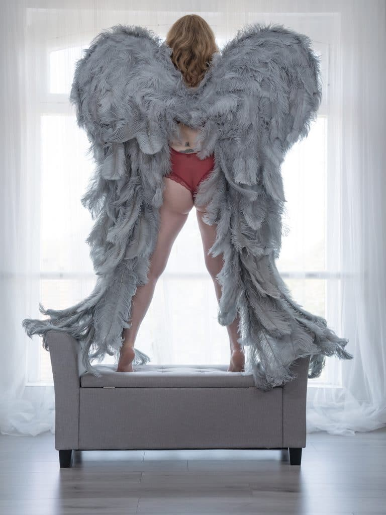 Woman with dramatic angel wings near a large window